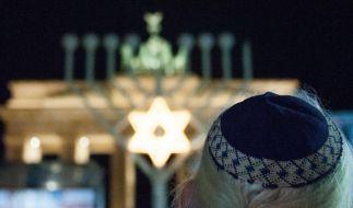 Auf dem Pariser Platz in Berlin vor dem Brandenburger Tor wurde am Dienstag die erste Leuchte des Chanukka-Leuchters durch Bundesinnenminister de Maizière entzündet. (Foto)