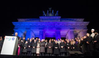 Mahnwache in Berlin: Bundespräsident Joachim Gauck spricht vor den Brandenburger Tor. Es leuchtet in den französischen Nationalfarben. (Foto)