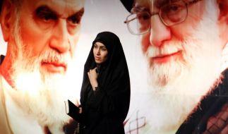 """Eine Iranerin vor riesigen Bildern von Ayatollah Ruhollah Khomeini (links) und Ayatollah Ali Khamenei: Irans oberste religiöse Führer wollen gegen """"Charlie Hebdo"""" protestieren. (Foto)"""