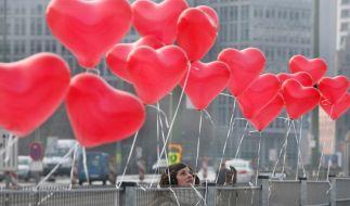 Eine junge Frau knotet in Berlin rote Herz-Luftballons zum Valentinstag an einen Zaun. (Foto)