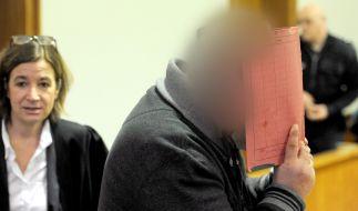 Der ehemalige Krankenpfleger Niels H. versteckt sein Gesicht hinter einem Aktendeckel, während er am 12.02.2015 den Sitzungssaal des Landgerichtes in Oldenburg (Niedersachsen) betritt. (Foto)