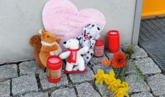 """Blumen, Kerzen, Stofftiere und ein Papierherz mit der Aufschrift """"Du bleibst immer in unseren Gedanken"""" liegen in Unterföhring bei München (Bayern) vor einem Hauseingang. (Foto)"""