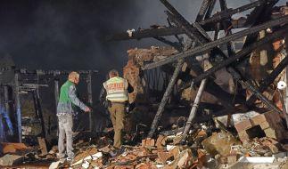 Die Rettungskräfte stehen vor den Trümmern des zerstörten Hauses. (Foto)
