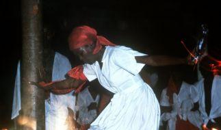 Eine Frau tanzt in der Glut eines brennenden Feuers bei einer Voodoo-Zeremonie. (Foto)