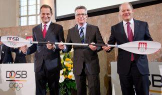 DOSB-Präsident Alfons Hörmann (l), Bundesinnenminister Thomas de Maiziere (m, CDU) und Hamburgs Erster Bürgermeister Olaf Scholz (SPD, r) halten während der Mitgliederversammlung des DOSB ein Paddel mit dem Wappen von Hamburg in den Händen. (Foto)