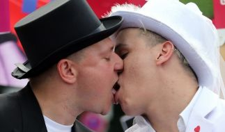 In Hochzeitskleidung küssen sich diese beiden Männer in Berlin am Christopher Street Day. (Foto)