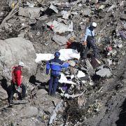 Einsatzkräfte suchen zwischen den Trümmerteile nach den Überresten der Opfer.