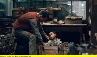 Pippig (Florian Stetter) hält den kleinen Jungen (Vojta Vomácka) versteckt. (Foto)
