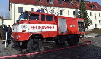 Einsatzkräfte von Feuerwehr und Polizei stehen vor der zukünftigen Unterkunft für Asylbewerber in Tröglitz. (Foto)