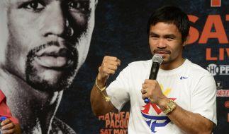 Manny Pacquiao vor einem Poster seines Konkurrenten Floyd Mayweather. (Foto)