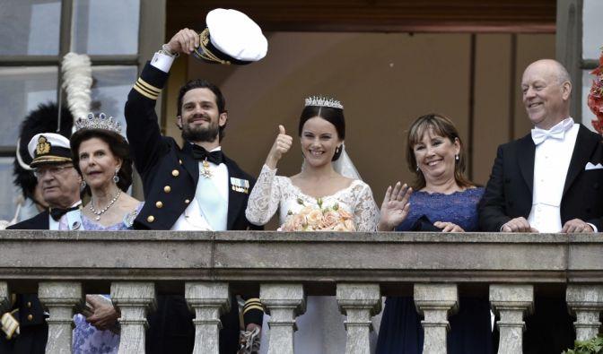 Ehepaar und Brauteltern winken vom Balkon.