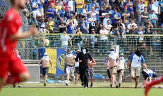 Chaoten stürmen während des Spiels den Platz. (Foto)