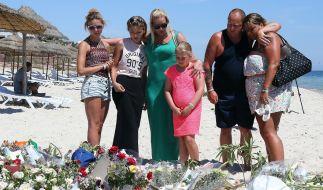 Touristen legen am Strand von Sousse Blumen nieder nach dem blutigen Attentat am vergangenem Freitag. (Foto)