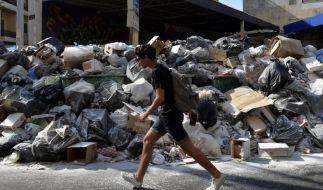 Ein junger Mann läuft durch eine zugemüllte Straße in Beirut. Schon seit Juli gibt es Problem mit der Müllentsorgung. Am 17. August wurde die größte Mülldeponie der Stadt ersatzlos geschlossen. Seitdem verschärft sich die Situation. (Foto)