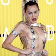 Miley Cyrus nutzt ihre Gastgeberrolle bei den VMAs um sich in einige gewagte Outfits zu werfen.