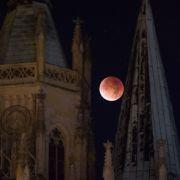 Der rötlich gefärbte Mond leuchtet am 28.09.2015 in Erfurt (Thüringen) hinter dem Dom.