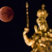 Der Mond erscheint am 28.09.2015 neben der Marinefigur im Zentrum von München (Bayern) rötlich.