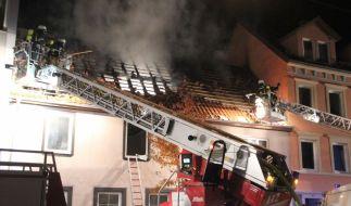 Feuerwehrleute sind in der Nacht in Pforzheim (Baden-Württemberg) bei einem Dachstuhlbrand im Einsatz. Nach ersten Angaben sind bei dem Brand des überwiegend von Ausländern bewohnten Hauses vier Menschen ums Leben gekommen, weitere wurden verletzt. (Foto)