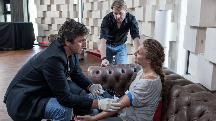 Dr. Martin Gruber (Hans Sigl) untersucht Katharina Herz (Alessija Lause), die auf dem Sofa vor ihm sitzt. (Foto)