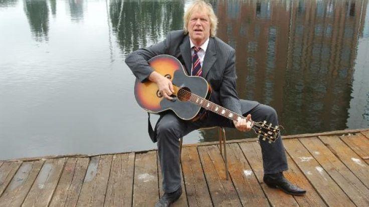Gunter Gabriel sitzt im Harburger Hafen südlich von Hamburg auf der Terrasse seines Hausboots mit einer Gitarre. (Foto)