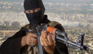Maskierter Terrorist posiert mit einem Sturmgewehr. (Foto)