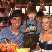 Philipp Lahm (l), seine Frau Claudia und Sohn Julian feiern in München beim traditionellen Besuch der Mannschaft des FC Bayern München auf dem Oktoberfest.