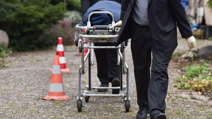 Mitarbeiter eines Bestattungsunternehmens transportieren am 10.02.2016 in Alsbach-Hähnlein (Hessen) eine Leiche aus einem Wohnhaus. (Foto)