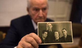 Der Auschwitz-Überlebende Leon Schwarzbaum zeigt ein altes Foto, das ihn selbst (l) neben seinem Onkel und seinen Eltern zeigt, die alle drei in Auschwitz ums Leben kamen. (Foto)