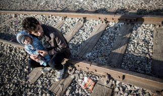 Warten, bis es weitergeht. Ein irakischer Flüchtling sitzt mit seinem Baby in Idomeni, an der Grenze zwischen Griechenland und Mazedonien. Seit Montag ist die Lage in dem Grenzort kritisch. Mazedonien lässt keine Menschen mehr passieren. (Foto)