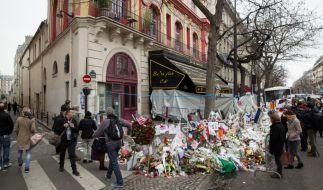 """Passanten legen nach den Pariser Anschlägen am 15. November 2015 Blumen vor dem Musikclub """"Bataclan"""" nieder. (Foto)"""