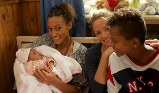 Hebamme Lena (Patricia Aulitzky, Mitte) zögert nicht lange und nimmt Senait (Sabrina Ceesay, links) und ihren Sohn Anbessa (Ruben Felipe, rechts) bei sich auf, die aus Eritrea geflüchtet sind. (Foto)