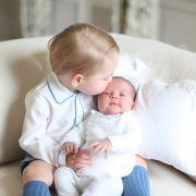 Der stolze Bruder gibt seiner kleinen Schwester einen zärtlichen Kuss auf die Stirn.