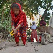Ein Mädchen aus Peshawar schneidet einer toten Ratte den Schwanz ab.