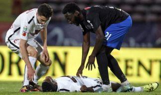 Sein Mitspieler Ratariu (l) sowie Gegner Buzbjuchi (r) versuchen, Patrick Ekeng nach einem Kollaps zu helfen. (Foto)