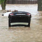 Nur die offene Kofferraumklappe eines Fahrzeuges ragt in Triftern (Bayern) noch aus dem Hochwasser.