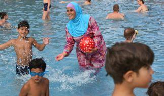 Die Berlinerin Abir am 20. August 2012 in einem Freibad in Berlin mit ihren Kindern. Sie trägt einen Burkini. Im bayerischen Neutraubling ist das Tragen eines solchen nun nicht mehr gestattet. (Foto)