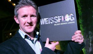 Jens Weißflog zeigt sein Buch. (Foto)