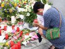 Vor dem Olympia-Einkaufszentrum in München: Eine Frau kniet weinend vor Kerzen und Blumen. (Foto)