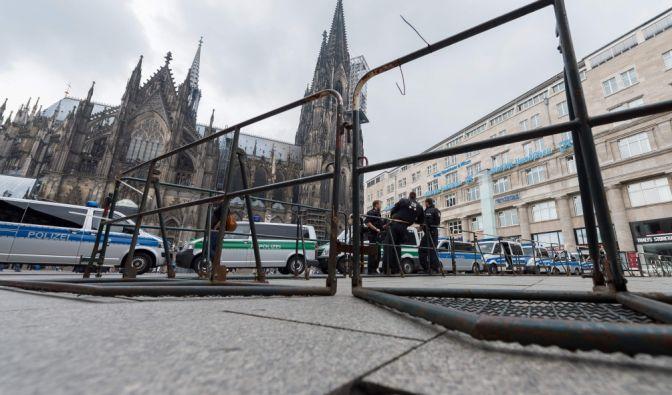 Polizeibeamte stehen am 31.07.2016 vor dem Dom in Köln (Nordrhein-Westfalen) und sperren den Hauptbahnhof ab. Vom Hauptbahnhof startet die Gegendemonstration von PRO NRW gegen die Erdogan Anhänger.