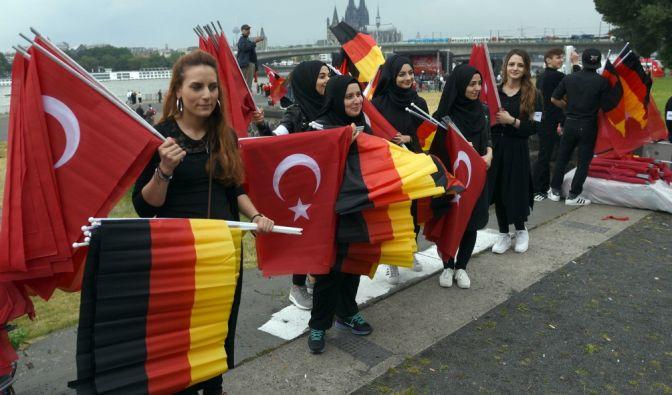 Helfer verteilen vor dem Beginn der Kundgebung von Erdogan-Anhängern deutsche und türkische Fahnen.