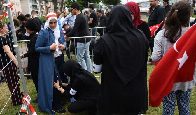 Helfer kontrollieren vor dem Beginn einer Kundgebung die Besucher.