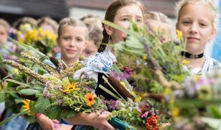 In Tracht gekleidete Mädchen tragen zu Maria Himmelfahrt in Kochel am See (Bayern) Kräuterbuschen in die Kirche. Alljährlich findet am 15. August der große Kocheler Heimattag statt. (Foto)