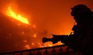 Ein Feuerwehrmann in Los Angeles versucht einen Brand zu löschen (Symbolbild). (Foto)