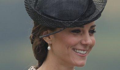 Woran erkennt man einen Royal schon aus der Ferne? Richtig, am extravaganten Kopfschmuck. Kate kombiniert hier einen schwarzen Fascinator-Hut mit einem dezenten Kleid aus beigefarbener Spitze.