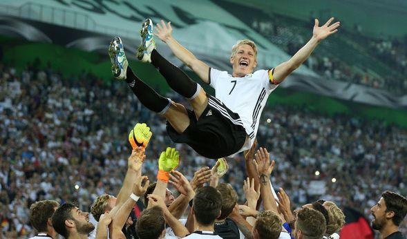 Die Mitspieler werfen Bastian Schweinsteiger von Deutschland nach dem 2:0 Sieg in die Luft.