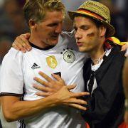 Bastian Schweinsteiger wird nach dem Spiel während der Ehrenrunde von einem Fan umarmt.