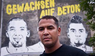 """George Boateng posiert vor einem Graffiti mit der Aufschrift """"Gewachsen auf Beton"""". (Foto)"""