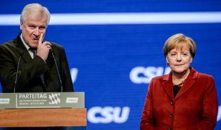 Angela Merkel lauscht am 20. November 2015 auf dem CSU-Parteitag in München der Rede des bayerischen Ministerpräsidenten Horst Seehofer. (Foto)
