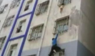 Ein Mann klettert die Wand eines Hochhauses hoch, um einen Jungen zu retten. (Foto)