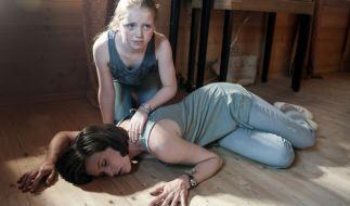 Katja (Sophie Melbinger) bricht vor ihrer Tochter Miriam (Anna Büttner) bewusstlos zusammen. (Foto)